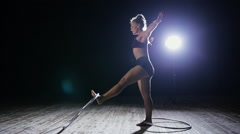 Acrobatic woman performer rotate hula hoop on dark scene Stock Footage