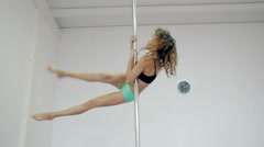 Wide shot Young girl dancing poledance in white room Stock Footage