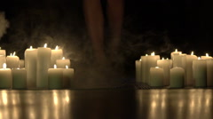 Girl's legs goes forward between fume of burning candles in darkness. Slowly Stock Footage