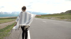 Young woman hitch-hiking on a road at the fields Stock Footage