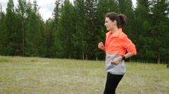 Woman running in wooded forest area, training and exercising for trail run Stock Footage