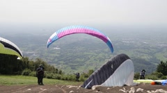 Some paragliders take-off from mountain Stock Footage