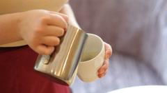 Pouring stream milk, barista prepares latte in cup Stock Footage