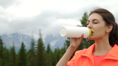 Runner holding bottle of water while resting after evening jog outside Stock Footage