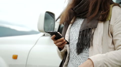 Woman using gps navigation on the smart phone near the car on the road Stock Footage