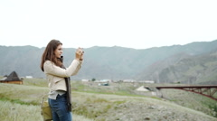 Young person relaxes on hiking in mountains and taking photo with mobile phone Stock Footage