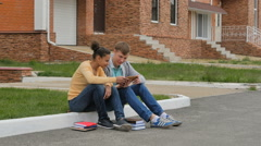 Couple teenagers sitting and playing a tablet. - stock footage