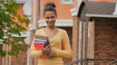 Young biracial holding notebooks and laughs. Stock Footage