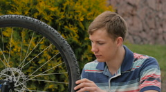The young man turns the wheel of the bicycle. Stock Footage