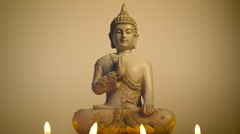Spritual Buddha statue lit by candle light against warm background Stock Footage