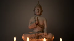 Centered meditating Buddha statue lit by candle light against dark background - stock footage