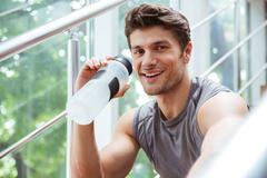 Happy sportsman drinking water in gym - stock photo