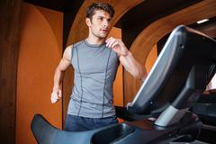 Young man in sportswear running on treadmill at the gym Stock Photos