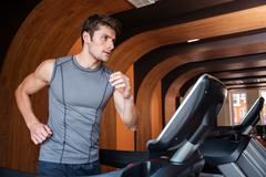 Man athlete running on treadmill in gym Stock Photos
