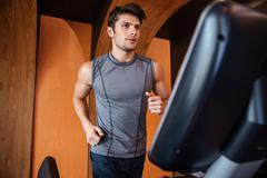 Serious young sportsman training and running on treadmill in gym Stock Photos