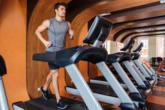 Fitness man working out and running on treadmill in gym - stock photo