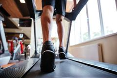 Back view of young sportsman running on treadmill in gym Stock Photos