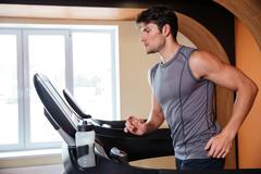 Man athlete warming up and running in treadmill in gym Stock Photos