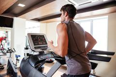 Back view of sportsman working out and running on treadmill Stock Photos