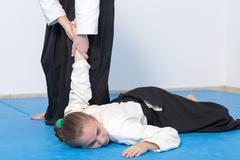 Two girls in black hakama practice Aikido - stock photo