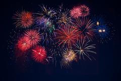 Beautiful celebration golden, red, blue sparkling fireworks over starry sky Stock Photos