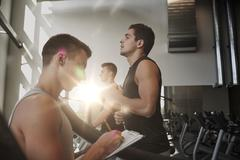 men exercising on treadmill in gym - stock photo
