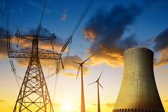 Nuclear power plant with wind turbines and electricity pylon in the sunset. - stock photo