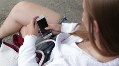 Young beautiful girl writes sms use smartphone Stock Footage