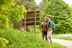 smiling couple at signpost with backpacks hiking - stock photo