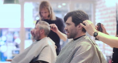 Hair stylist spraying water on the hair of his customer before giving a haircut Stock Footage