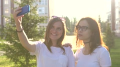 Beautiful girls friends taking selfies in the city sunset strong back light Stock Footage