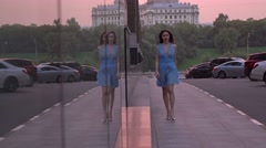Beautiful happy brunette girl in dress walking on the street against pink sunset Stock Footage