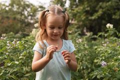 Little girl standing in the summer garden - stock photo