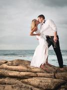 Eccentric Man and woman standing on rocks kissing passionately. Stock Photos