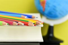 pencil crayons, books and terrestrial globe - stock photo