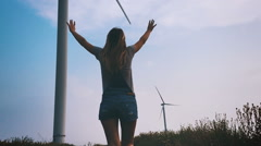 Happy girl running towards the wind turbine, slow motion. Stock Footage