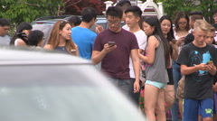 Young people playing Pokemon go game on their smartphones Stock Footage