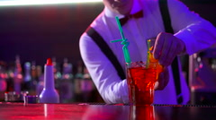 Hands of barmen inserts straw for cocktail in night club Stock Footage