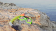 Tube and mask for diving on the cliff above the ocean Stock Footage