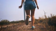 Happy girl running towards the wind turbine, slow motion. Stock Footage