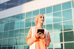 Portrait of an Arab businesswoman in hijab holding a tablet - stock photo