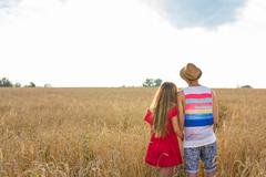 back view of a couple holding each other and contemplating landscape while - stock photo