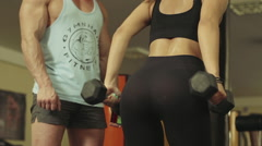 Girl doing exercise with dumbbells in the presence of a coach - stock footage