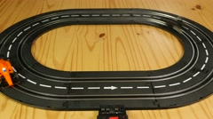 Toy car racing track with orange and black formula 1 cars Stock Footage