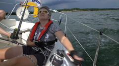 Sailing in the Baltic Sea. Yachtswoman raises the sail using a winch. Stock Footage