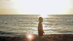 Little boy stay in calm sea at sunset - stock footage