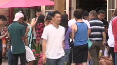 Crowds of people on main street playing Pokemon GO on their phones Stock Footage