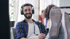 Creative businessman listening to music at his desk in a modern office Stock Footage