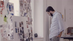 Young Business Executive looking at fashion photographs on wall Stock Footage