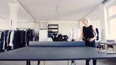 Fashion designer rolling fabric on table in her studio Stock Footage